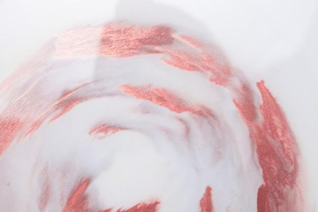 Vista dell'angolo alto delle macchie rosse della pittura isolate sul contesto bianco