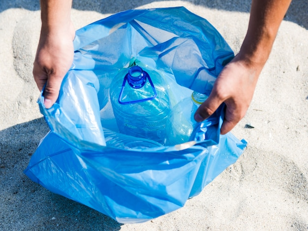 Vista dell'angolo alto delle mani che tengono la borsa di immondizia blu sulla sabbia
