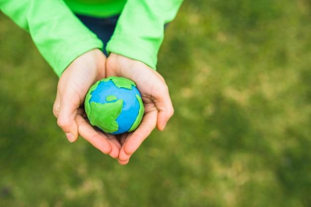 Vista dell'angolo alto delle mani di una ragazza che tengono il globo falso dell'argilla