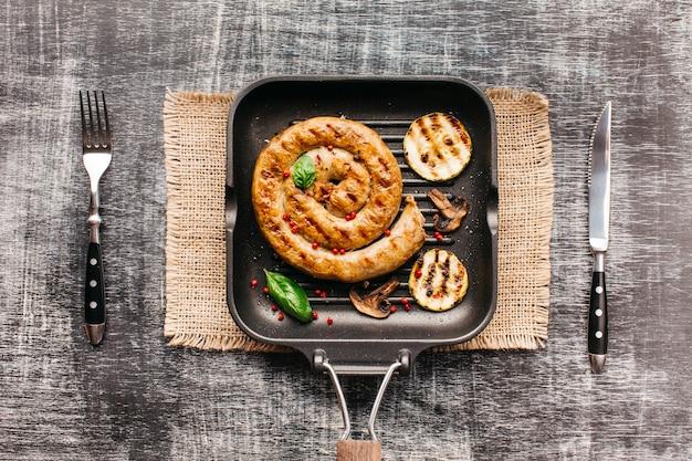 Vista dell'angolo alto delle salsiccie a spirale grigliate sulla vaschetta con la forchetta e il coltello di burro