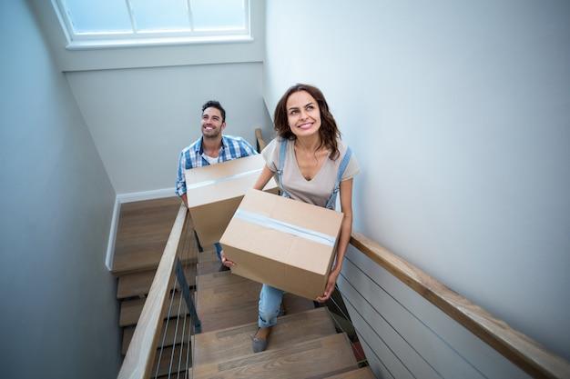 Vista dell'angolo alto delle scatole di cartone sorridenti della tenuta delle coppie mentre salendo i punti