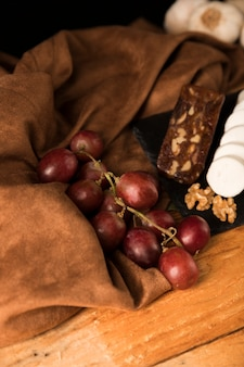 Vista dell'angolo alto delle uve rosse organiche sul panno marrone sopra la tavola di legno