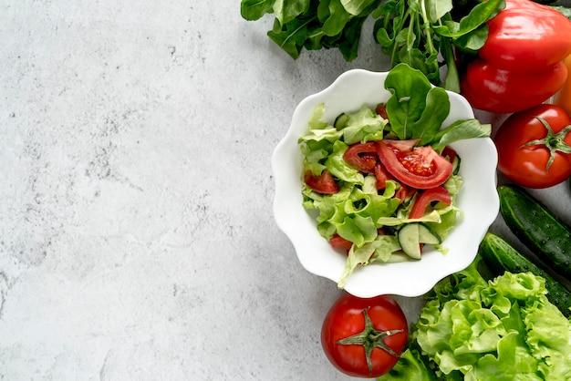 Vista dell'angolo alto delle verdure intere con la ciotola di insalata sopra il contesto strutturato