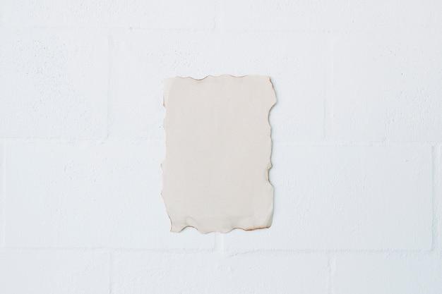 Vista dell'angolo alto di carta bruciata sopra la parete bianca