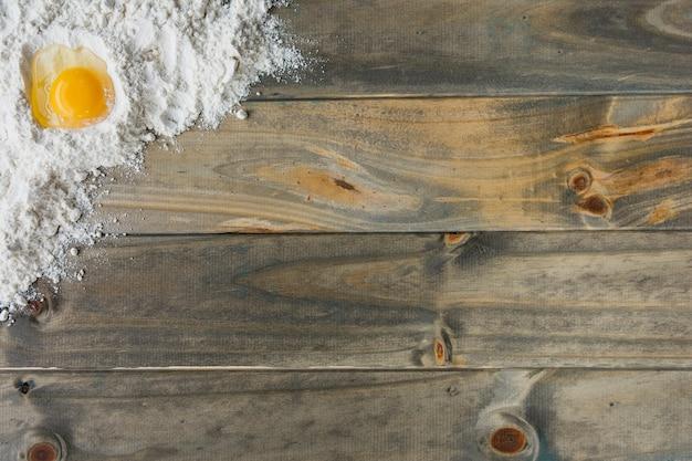 Vista dell'angolo alto di farina e dell'uovo su fondo di legno