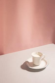 Vista dell'angolo alto di latte in tazza contro fondo rosa