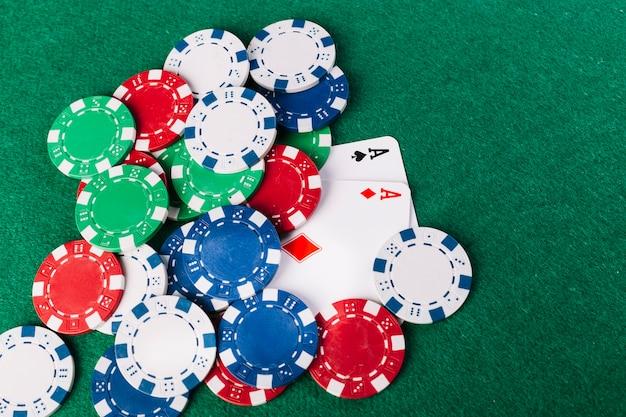 Vista dell'angolo alto di multi chip di mazza colorati e di due carte da gioco degli assi sulla superficie di verde