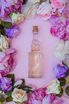 Vista dell'angolo alto di olio essenziale circondato con i fiori freschi su fondo rosa
