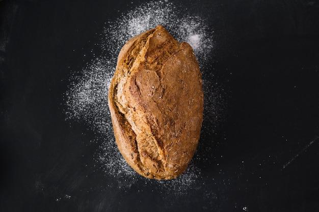 Vista dell'angolo alto di pane di recente cotto su fondo nero