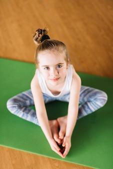 Vista dell'angolo alto di piccola ragazza che si esercita sulla stuoia verde