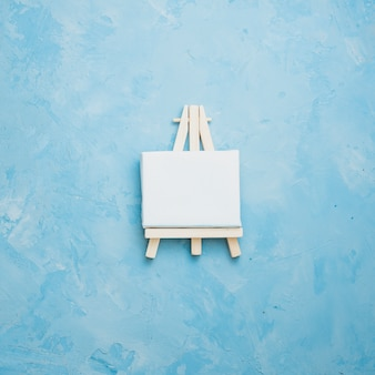 Vista dell'angolo alto di piccolo cavalletto miniatura su strutturato approssimativo blu