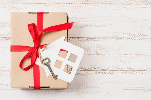 Vista dell'angolo alto di un contenitore di regalo legato con il nastro rosso sulla chiave della casa sopra la tavola di legno