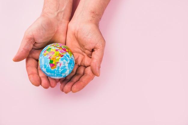 Vista dell'angolo alto di un globo sulle mani contro la superficie di rosa