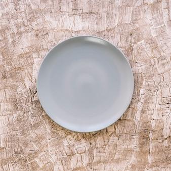Vista dell'angolo alto di un piatto vuoto su fondo di legno