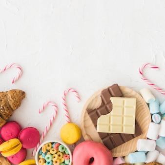 Vista dell'angolo alto di vari alimenti dolci su fondo bianco