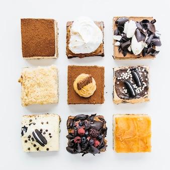 Vista dell'angolo alto di vari pasticcini deliziosi su fondo bianco