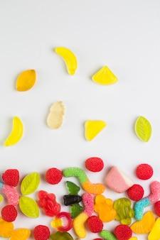 Vista dell'angolo alto di varie caramelle dolci su fondo bianco