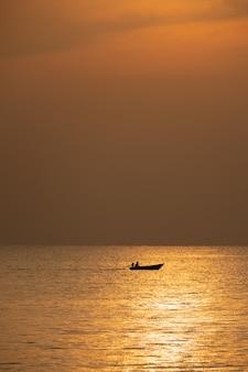 Vista della barca che galleggia sopra il mare con alba