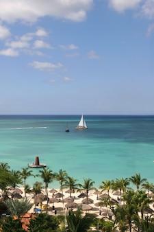 Vista della bellissima spiaggia tropicale con una barca a vela