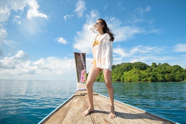 Vista della donna in costume da bagno godendo sulla barca longtail tradizionale tailandese sulla bellissima montagna e sull'oceano, le isole phi phi, thailandia