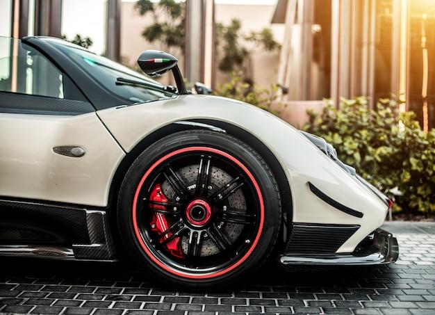 Vista della facciata frontale dell'automobile sportiva di colore grigio, argento con ruote rosse sulla strada.