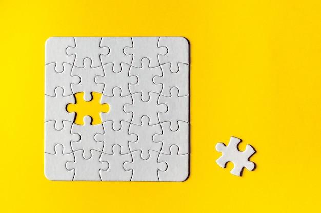 Vista della griglia bianca del puzzle su superficie gialla