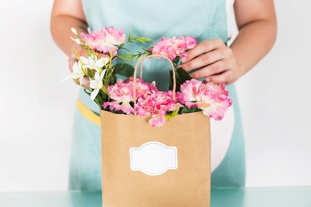 Vista della parte centrale del fiorista femminile con sacchetto di carta del fiore