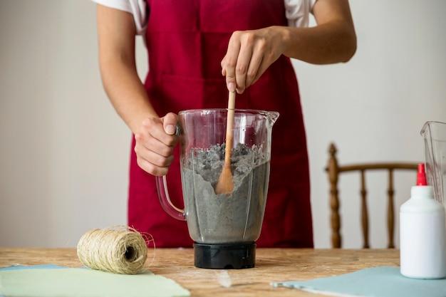 Vista della parte centrale della mano di una donna che rimuove la polpa di carta nel miscelatore