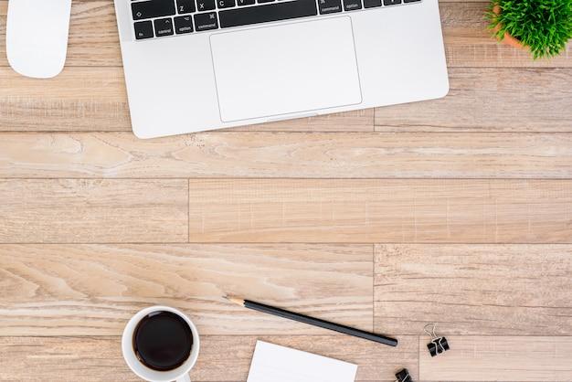 Vista della scrivania con computer portatile, topo, albero, clip nera, tazza di caffè, taccuino e matita
