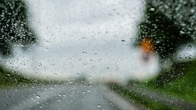 Vista della strada attraverso la finestra coperta di gocce di pioggia