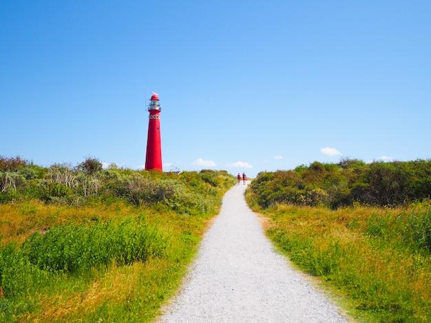 Vista della torre nord - faro nelle isole schiermonnikoog una delle isole frisone, sulla duna di sabbia contro il cielo blu
