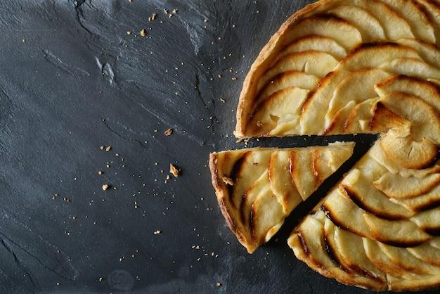 Vista della torta di mele a fette su ardesia con lo spazio del testo