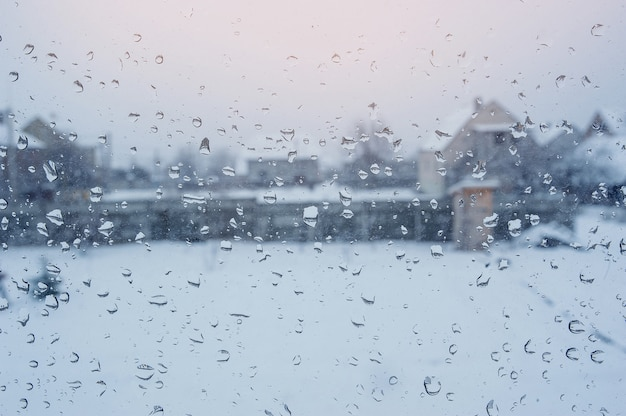 Vista delle case attraverso una finestra con gocce di pioggia