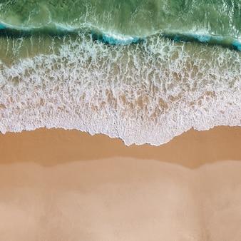Vista delle onde di schiuma di mare sulla riva
