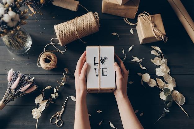 Vista di alto angolo della donna irriconoscibile che tiene un regalo fatto con amore, spago, carta kraft e fiori secchi sul tavolo