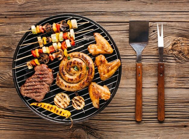 Vista di alto angolo di deliziose grigliate di carne con verdure oltre i carboni su un barbecue