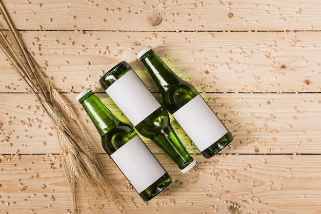 Vista di alto angolo di tre bottiglie di birra e spighe di grano su venatura del legno