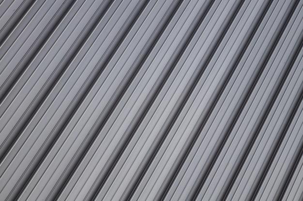Vista di angolo alla superficie ondulata grigia della parete o del recinto del metallo.