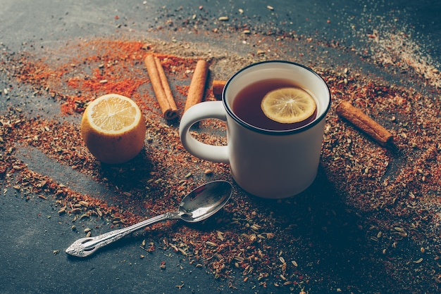 Vista di angolo alto tè al limone ed erbe secche con cannella secca, cucchiaio e limone
