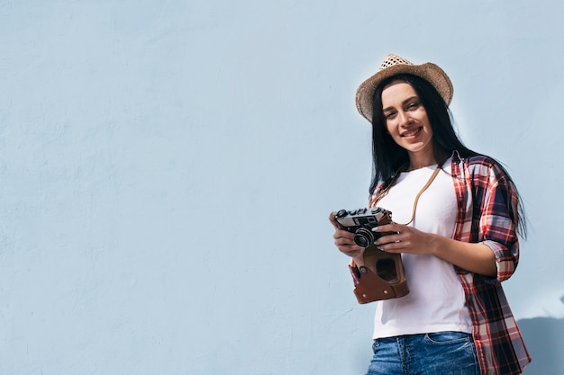 Vista di angolo basso del cappello da portare sorridente della donna che tiene retro macchina fotografica che si leva in piedi contro il cielo
