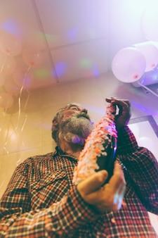 Vista di angolo basso dell'uomo senior che tiene la bottiglia dell'alcool a disposizione decorata con i coriandoli