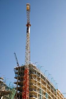 Vista di angolo basso della gru di costruzione vicino al sito contro cielo blu