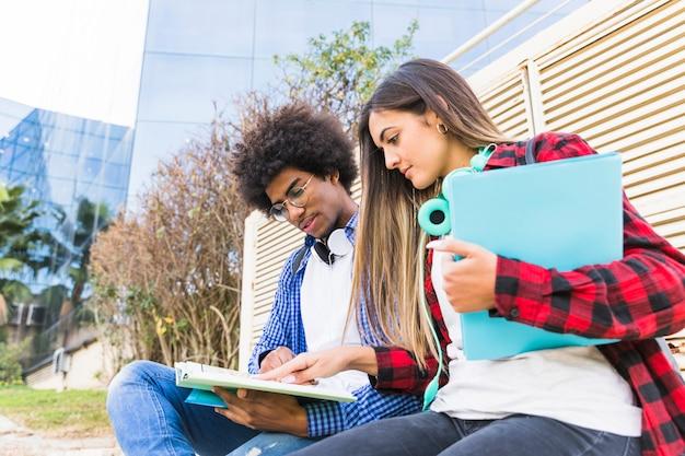 Vista di angolo basso di giovani studenti diversi che studiano insieme davanti all'edificio universitario