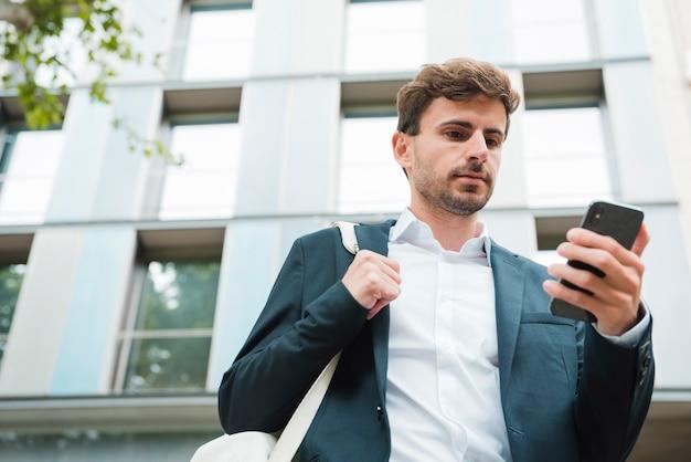 Vista di angolo basso di un uomo d'affari che sta davanti a costruzione che esamina telefono cellulare