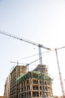 Vista di angolo basso di una costruzione con la gru di costruzione contro il cielo blu e bianco