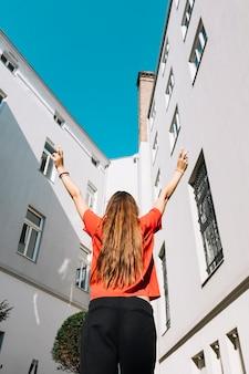 Vista di angolo basso di una donna che alza le sue braccia vicino all'edificio residenziale