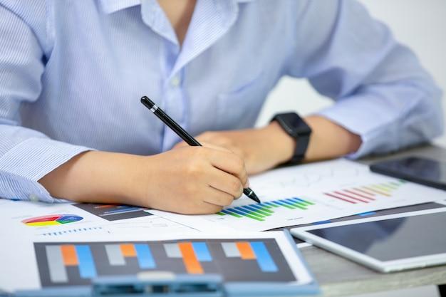 Vista di angolo laterale della gente di affari che scrive sui documenti sul tavolo