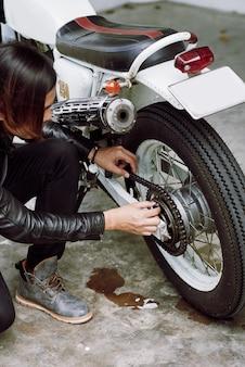 Vista di angolo superiore del motociclista che ripara la sua bici