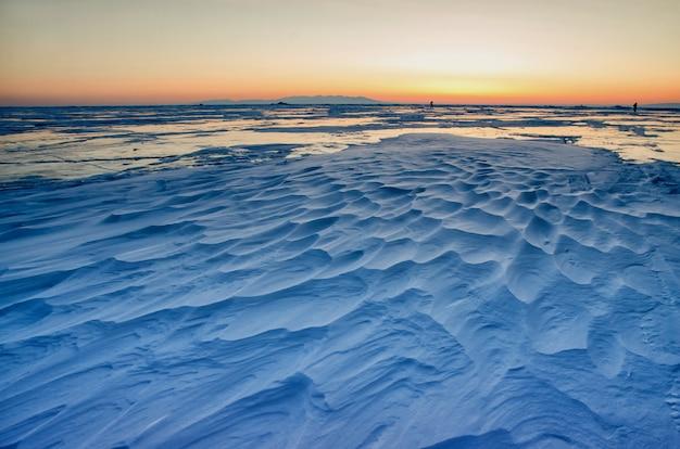 Vista di bei disegni su ghiaccio dalle crepe e dalle bolle di gas profondo sulla superficie del lago baikal nell'inverno, russia