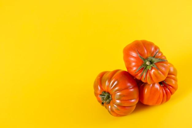 Vista di bei pomodori rossi di cimelio di famiglia su giallo